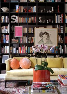 just plain good.  living room. love the bookshelves and the art and the round peach pillows on the lemon sofa!