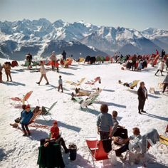 Holiday-makers take the sun on a mountain top in Verbier, 1964. Poster Print by Slim Aarons at the Condé Nast Collection