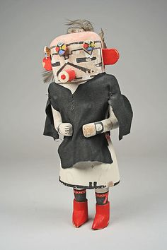 Navan (or velvet shirt) kachina tihu, Hopi. Colton 171 [jcx]. Case mask, tube mouth, rectangular eyes, inverted V over mouth. Four flowers on head.. Said to be a Zuni type introduced after 1900. Earl and Kennard 1938.