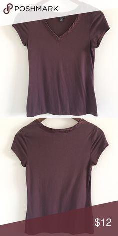 """🆕 Banana Republic Satin Trim V-Neck T-Shirt A gorgeous plum v-neck tee with satin trim at the neckline 💜  Stats (laying flat): Length: approx. 21.5""""   Width (pit to pit): 15""""   Blend of rayon, lyocell, cotton, spandex  Pre-owned, with minimal signs of wear   Hand wash cold or dry clean   No trades Banana Republic Tops Tees - Short Sleeve"""