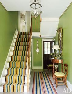 Interior designer Bruce Shostak and his partner, Craig Fitt, decorated the entrance hall of their circa-1817 house in Claverack, New York, in a lively and period-perfect Federal style. The front door opens to walls painted a vibrant apple-green, mismatched striped runners by Woodard & Greenstein, and tiger-maple antiques that match the original banister.