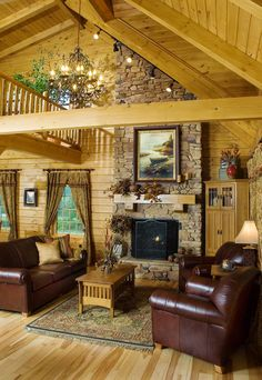 This log home great room is in the McKay Model Home by Hochstetler Log Homes. With a cathedral ceiling, exposed beams, a stone fireplace, and an open concept, this great room is the perfect place to spend down time or to entertain guests. #loghomes #logcabin #exposedbeams #greatroom