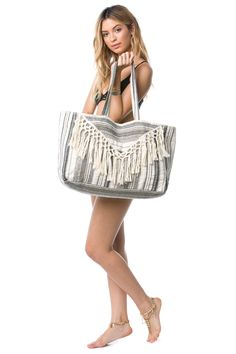 The Sol Tote Bag is a cotton and lurex yarn dyed beach bag lined in cotton poplin with macramé fringe detail, metal snap closure and inner zip pocket.
