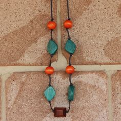 Stylish wooden jewellery inspired by my love of nature and the earthy colours of our beautiful planet. Handmade leather cord necklace featuring orange beads, teal beads and tan beads. A statement necklace which can be worn day or night.