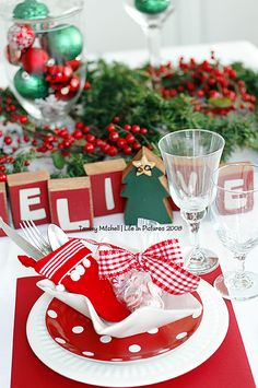 A classic Christmas dinner party with bright shades of red and green.  Star bowls and polka dot salad plates from pottery barn.  Stocking silverware holders Crate and Barrel, soft king leo peppermints in celophane bags tied with fun red and white gingham ribbon serve as fun table decorations and party favors.    Tammy Mitchell Southern California www.tammymitchell.typepad.com