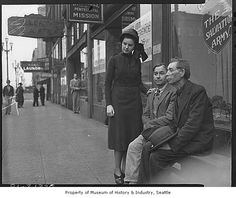 May 1940 photo shows Ruth Clarke, a Salvation Army worker, and two unidentified men outside the group's mission at 213 Second Avenue South, near Pioneer Square. In 1940, Salvation Army workers ran seven halls in Seattle.