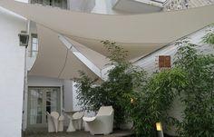 Superposition de 3 voiles triangulaires Umbrosa dans un jardin de ville - pose par COTE TERRASSE