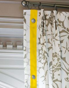 To blur the edges of grids on the paneling and windows, elegant drapery panels in a gray-and-white burnout floral pattern cascade from moldings to the floor. A width of yellow grosgrain ribbon trimming the edges of each panel unites the other jolts of yellow. The ribbon is pierced with silver nailheads that give the draperies a measure of metallic shine.