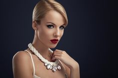 Beauty - Beautiful blonde with red lipstick and the necklace around the neck posing in the studio