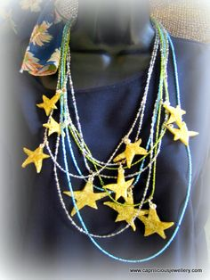 """A pretty, light hearted piece - 6 long strands of multicoloured seed beads, carrying 10 polymer clay stars with a faux ceramic finish. The beads are both transparent silver lined, and opaque, in blue, green and grey/lilac/silver colourways, with brown Picasso jasper beads used on either side of each star as spacers. The longest strand is 17"""" long and the shortest, 11"""". The stars are individually drawn 5 pointed stars in different sizes, £25"""