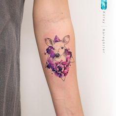 Tatuagem criada por KORAY KARAGÖZLER da Turquia. Cervo com moldura triangular e flores coloridas.