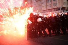 DIRECT HIT: Police officers took cover as protesters shot fireworks at them during clashes in Istanbul on Saturday. Two protesters were killed on Friday in clashes with Turkish police that erupted over claims that Kurdish rebel cemeteries had been destroyed, local media reported. (Bulent Kilic/AFP/Getty Images)
