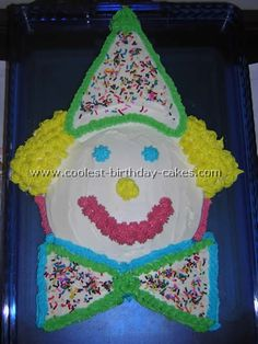"Homemade Circus Clown Cake ""I used white cake mix & made 1 round cake & 1 square cake from the mix. The circle was the face & we cut the square into pieces to make the triangle hat, triangle bow tie and the extra pieces for the hair. I decorated it using canned frosting all over the cake as a base. I colored with Wilton decorator frosting and made the outlines, hair, eyes, nose and mouth. I put colored sprinkles on the hat & bow tie for a circus clown confetti look."""