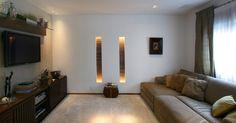 """Com 15,5 m�, este projeto de Karina Korn propicia conforto aos usu�rios: a parede, que foi revestida com papel, acomoda a TV LED 42"""". Acima do aparelho, a prateleira de vidro instalada no painel de madeira apoia objetos e plantas. Abaixo, o grande m�vel com portas ripadas armazena os equipamentos eletr�nicos, al�m de livros. Amplo, o sof� retr�til combina com o tapete e a cortina e o forro embute luzes pontuas e caixas de som"""