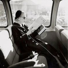 Mrs. William McManus, Vogue fashion editor, seated in train reading, wearing coat, sunglasses, and hat. Ca. 1955. Image by Condé Nast Archive/CORBIS