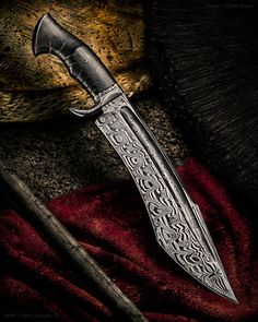 "Maker: Sam Lurquin, JS Website: samuel-lurquin.com Blade Length: 12"" Overall Length: 17"" Handle: Ancient bog oak Blade Material: ""BadasSam"" damascus Hilt: ""Shock twist"" damascus"