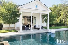 The pool house echoes the grand Georgian architecture of the main estate, though the columns offer a more casual welcome thanks to the comfortable restoration Hardware furniture positioned right at the entrance. The pool is by Shoreline Pools.