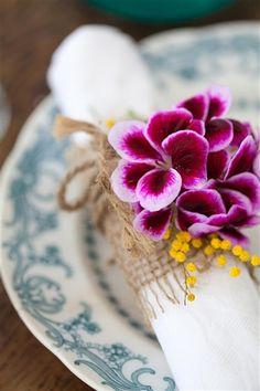 En remsa säckväv runt servetten, hopknuten med ett natursnöre och en blomma, här med pensepelargon.