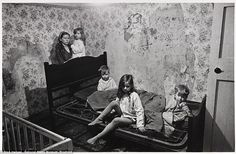 Squalor: Mrs M huddles with her four young children in the council house that they share with her husband in Balsall Heath, Birmingham. Their home has no bathroom, no hot water and the inside walls are running with damp. The children slept on sodden seat cushions covered by a couple of old 'macs'. They are pictured in January 1969, when a thick layer of snow lay outside and the windows were broken