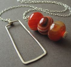 3 bead lariat necklace. Good idea.  Instead of a round link or knotted loop, use a rectangle.  Simple but different.