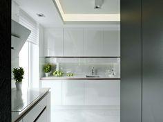 Aranżacja wnętrza kuchni w apartamencie w Warszawie. Jest to ascetyczne białe wnętrze w nowoczesnym funkcjonalnym stylu.