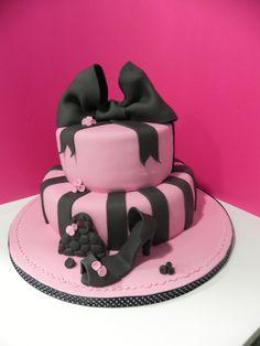 Tarta  personalizada en tonos rosa y negro con una gran lazada negra. Zapatos y bolso modelados en fondant elaborada por TheCakeProject en Madrid