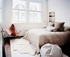 """Layered area rug. White bedding. Grown up versions of """"kids furniture."""" Bean bag chair. Butterfly chair. White painted brick. Reading lamp. Dark wood floors."""
