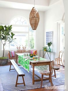 A simple antique table is enlivened with an embroidered Mexican cloth. Design: Nickey Kehoe.