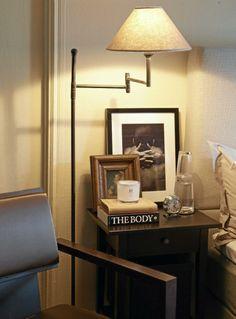Nattbordet er dekorert med lekre fotografier, en vekkerklokke og lesestoff. En gulvlampe står for leselyset.