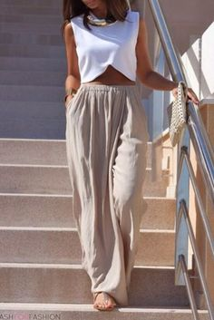 Nude pants paired with a white crop top, gold necklace and clutch and sandals.