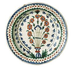 AN OTTOMAN POTTERY DISH (TABAK), IZNIK, TURKEY, CIRCA 1590  With a sloping rim, the white interior decorated with a large central bouquet of red carnations flanked with hyacinthes $60,073.00