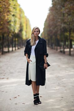 ELIZABETH in a navy wool trench coat, cream skirt, and black clutch.