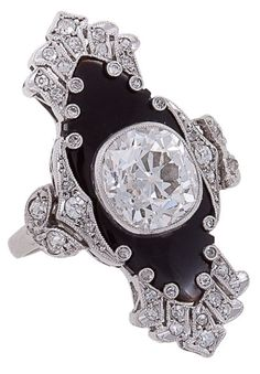 Art Deco Diamond, Onyx & Platinum Ring. One of a kind Art Deco ring centering a large bezel-set, cushion-shaped full-cut diamond, 3.10 carats, color: I-J, clarity: VS2, surrounded by onyx and intricate platinum work set with 40 single-cut diamonds weighing approximately .42 carats. Head of ring measures approximately 1 1/4 inches vertically.  Via 1stdibs.