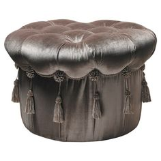 Tufted velvet ottoman in brown with hanging tassels.  Product: OttomanConstruction Material: Wood and velvet