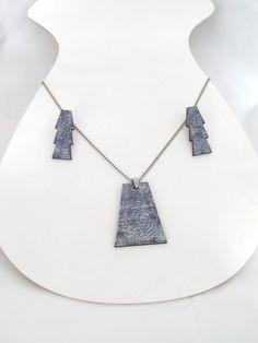 Conjunto em MDF, nas cores azul e prata, pintados a mão. Acabamento em metal. Colar 43 x 4,5 cms = R$ 36,00 Brinco 1,5 x 5 cms = R$ 27,00 As peças são vendidas separadamente. Designer Exclusivo R$57,00