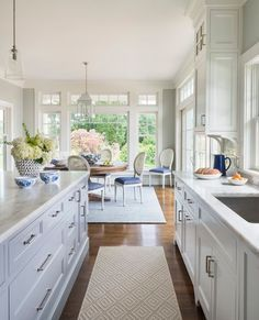 Crisp white kitchen with an open floor plan and a large island. Kitchen goals.