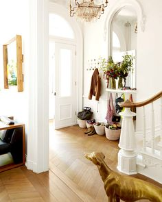 Grand entryway of white, traditional home with baskets for outerwear and coat hangers