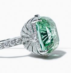 A vibrant green tourmaline sparkles within a setting of round brilliant diamonds.