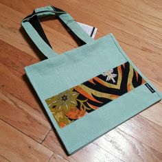 NWT Fair trade Structured Jute Tote Beautiful, handcrafted aqua jute tote. The jute is laminated inside and straps are cotton lined. Metal snap closure. Measurements provided in photos. Will easily fit an iPad, magazine, and much more. Structured tote and will stand on its own when filled.  Fabric design is on both sides of the bag. Fair Trade Bags Totes
