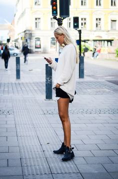 Rockin booties, and an oversized sweater make black denim shorts a transitional piece for the Fall.