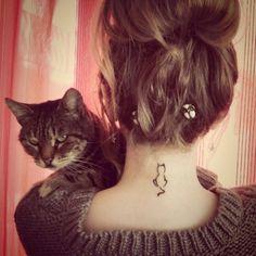 Chica cargando a un gato mientras muestra su tatuaje en la nuca en forma del contorno de un gato