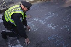PHOTOS: TWO EXPLOSIONS AT BOSTON MARATHON FINISH LINE   Boston police officer Pat Duggan wrote in chalk outside a makeshift memorial along Newbury street.