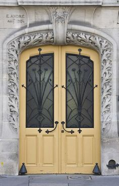 There 's something so charming about the moldings on this doorway. Doesn't this door remind you of something out of a fairy tale? The wrought iron details are great!
