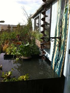 Water feature by Jeni cairns using a recycled grain auger rain spiral and water tank for the artisan retreat garden
