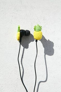 A pair of earbud headphones featuring a pineapple cutout design and a solid cord.