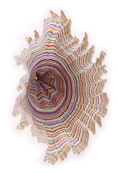 L'artiste Jen Stark fait des sculptures en piles de feuilles de papier ordinaires et les découpes pour révéler des couches psychédéliques et géométriques multicolores.