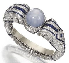 Indian inspired ART DECO bracelet. All platinum set with diamonds, featuring two elephant heads that hold a large cabochon star sapphire.