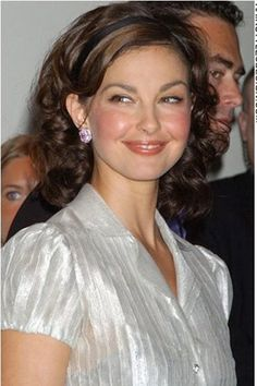 Ashley Judd's hair is long, thick and curly. There is so much volume to her hair. The hair is styled back behind her ears with no fringe at the forehead. This leaves her face clear and clean of any stray hairs.This haircut is long and layered.The hair colouring is medium brown.