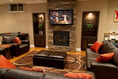 Captivating Modern Basement Ideas With Cozy Leather Couch Combined Orange Cushions And Espresso Table Featuring Black Glass Fire Place Under LCD TV Attached Natural Stone Walls Design. The natural stone walls open this media room basement. The fireplace under the media screen offers warmth ambiance. Living Room has a perfect design with maximum placement in every corner of the room.
