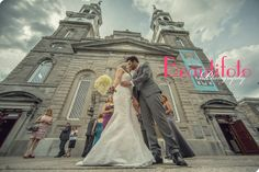 the bride and groom kissing in front of the church